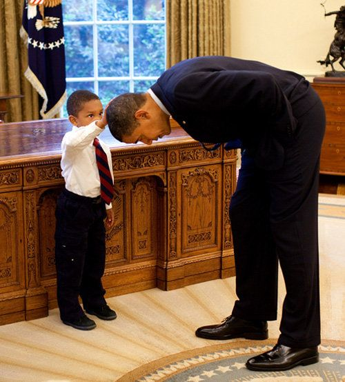 President Obama bends to 5-year-old Jacob Philadelphia, whose arm raised to touch the president's hair — to see if it feels like his.